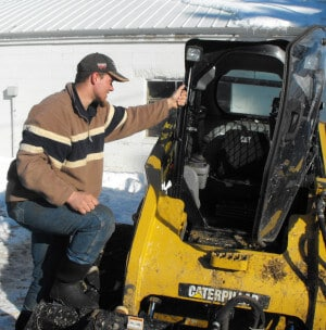 Man climbing into a skid steer