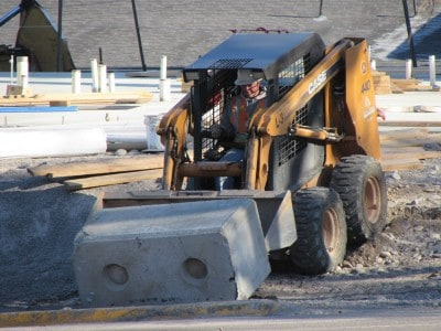 A man using a skid steer to move a cement block.